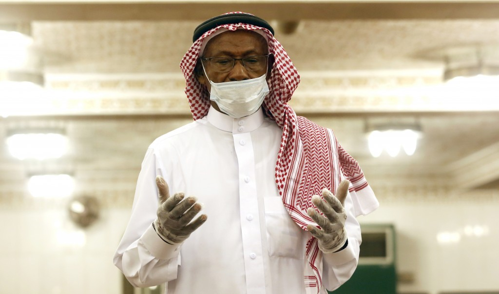 A Saudi worshipper wearing a face mask and gloves as he prays dawn prayers at al-Mirabi Mosque in Jiddah, Saudi Arabia, Sunday, May 31, 2020. The Mini...