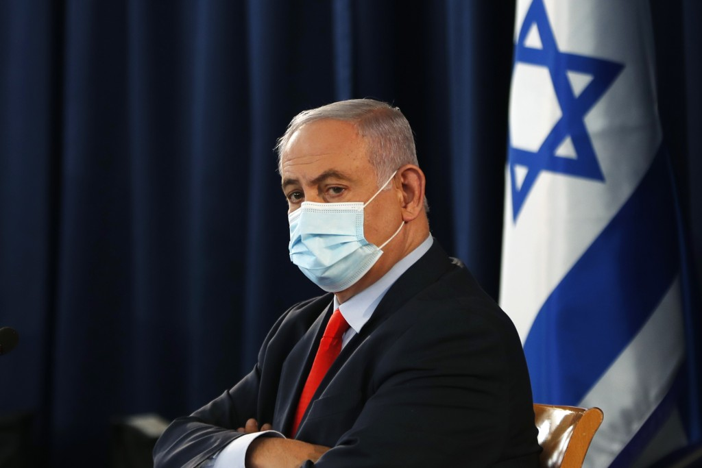 Israeli Prime Minister Benjamin Netanyahu wears a mask as he looks on during the weekly cabinet meeting in Jerusalem Saturday, May 31, 2020. (Ronen Zv...