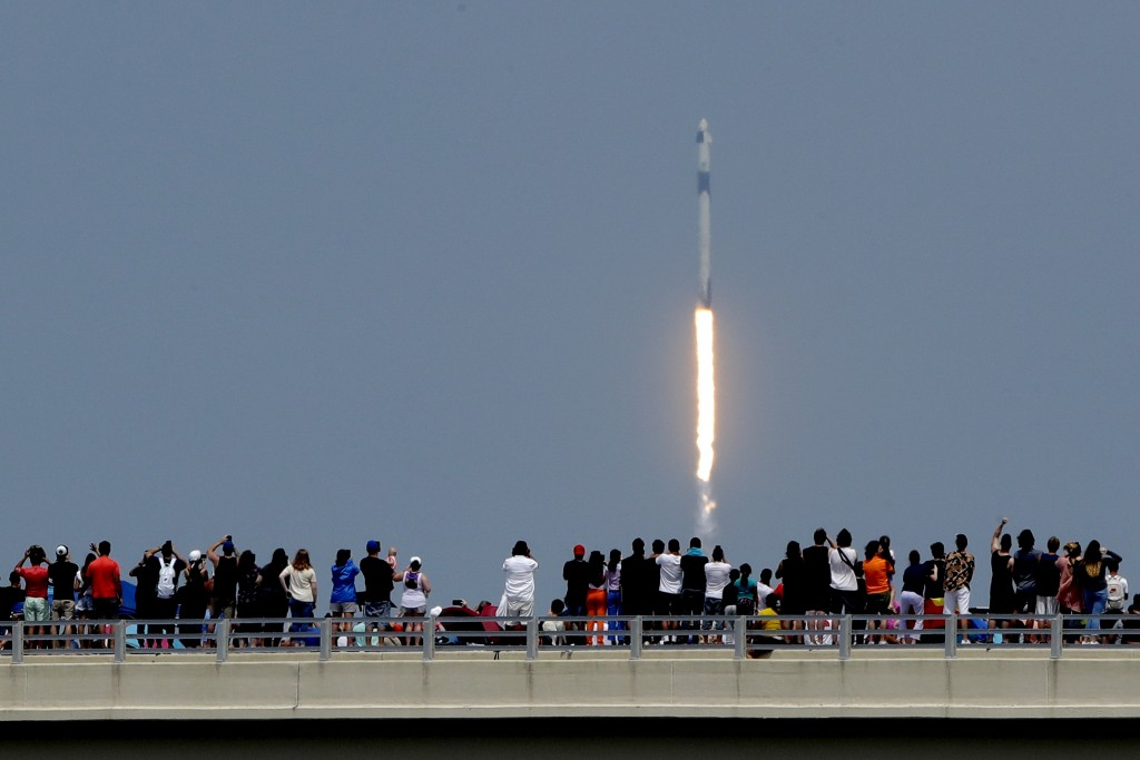 Spectators watch from a bridge in Titusville, Fla., as SpaceX Falcon 9 lifts off with NASA astronauts Doug Hurley and Bob Behnken in the Dragon crew c...