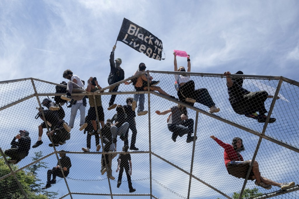 People stand on top of a baseball backstop during a protest over the death of George Floyd in Los Angeles, Saturday, May 30, 2020. Protests across the...