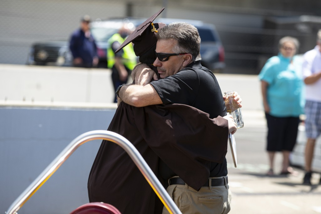 Ted Foxworthy, right, hugs his son Jacob Foxworthy as they walked off the track where he received his Speedway High School diploma during a ceremony a...