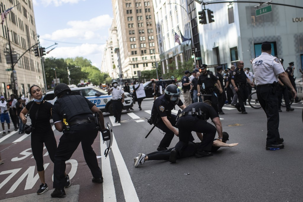 Police detain protesters in front of Trump Tower during a solidarity rally for George Floyd, Saturday, May 30, 2020, in New York. Demonstrators took t...