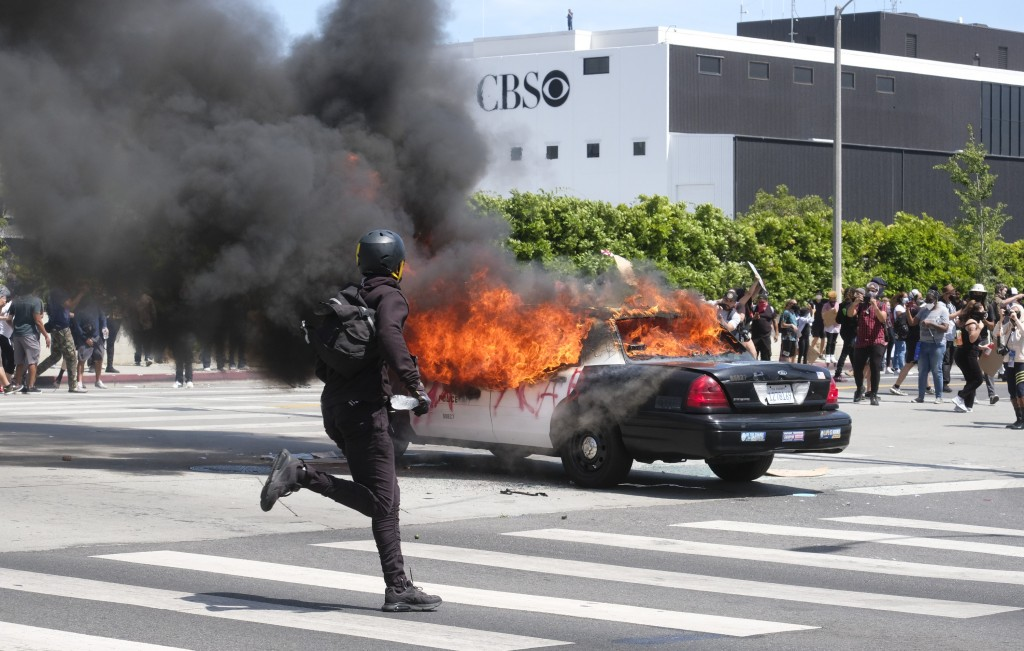 A person runs while a police vehicle is burning during a protest over the death of George Floyd in Los Angeles, Saturday, May 30, 2020. Protests acros...