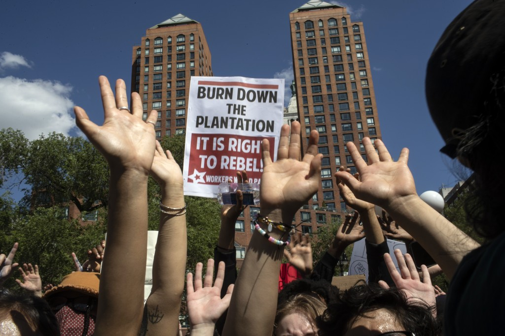 Protesters raise their hands in a solidarity rally for George Floyd, Saturday, May 30, 2020, in New York. Demonstrators took to the streets of New Yor...