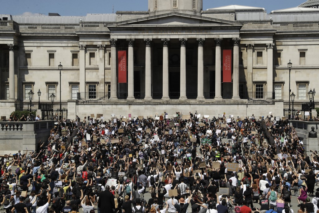 People, some of them kneeling gather in Trafalgar Square in central London on Sunday, May 31, 2020 to protest against the recent killing of George Flo...