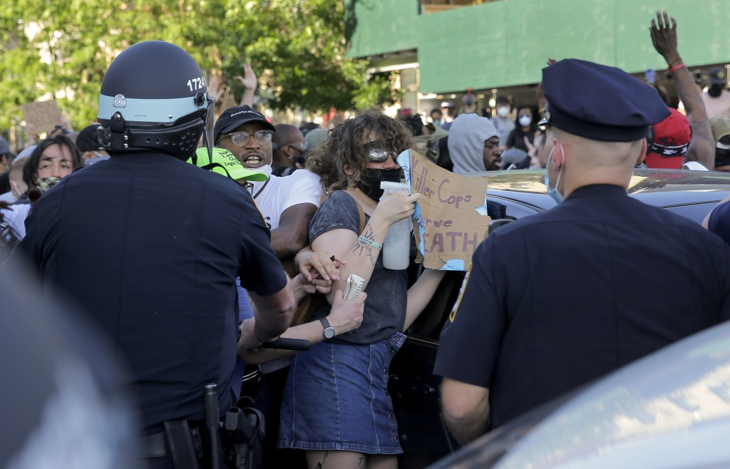 New York Police officers push back protesters during a demonstration Saturday, May 30, 2020, in the Brooklyn borough of New York. Protests were held t...