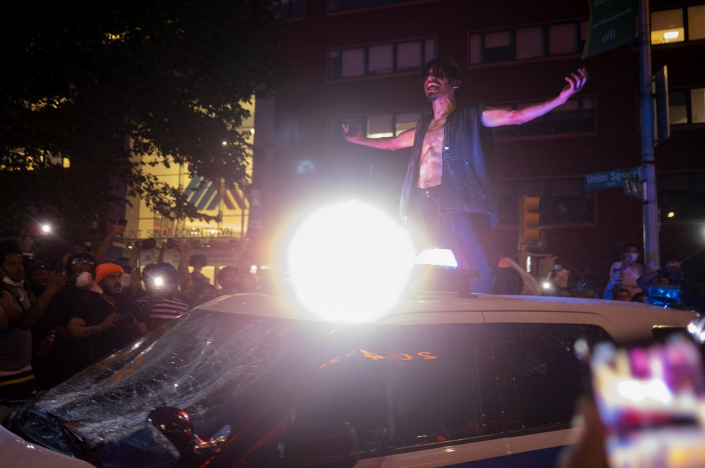 A protester gestures atop a damaged police vehicle near New York's Union Square, Saturday May 30, 2020, during a demonstration against the death of Ge...