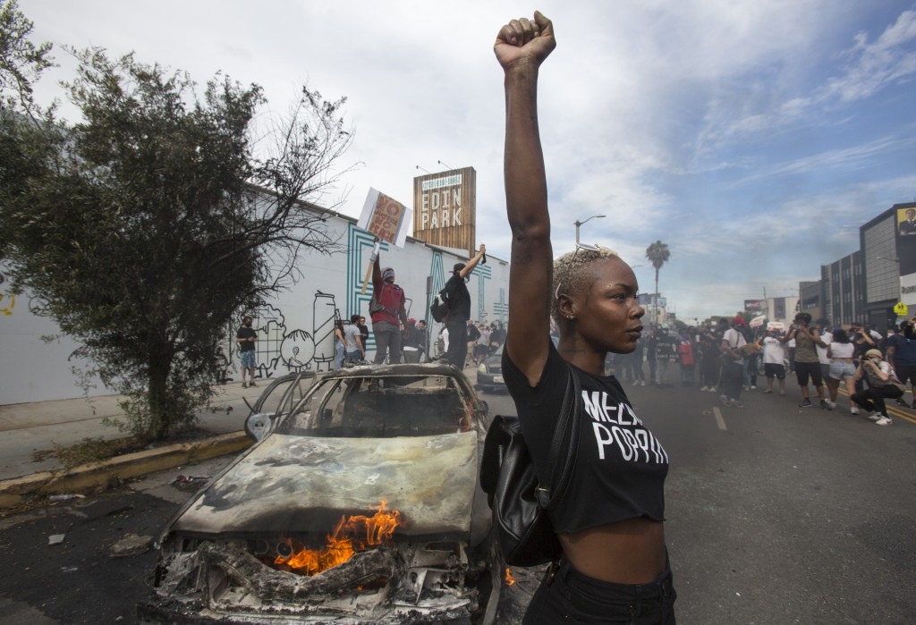 A protester poses for photos next to a burning police vehicle in Los Angeles, Saturday, May 30, 2020, during a demonstration over the death of George ...