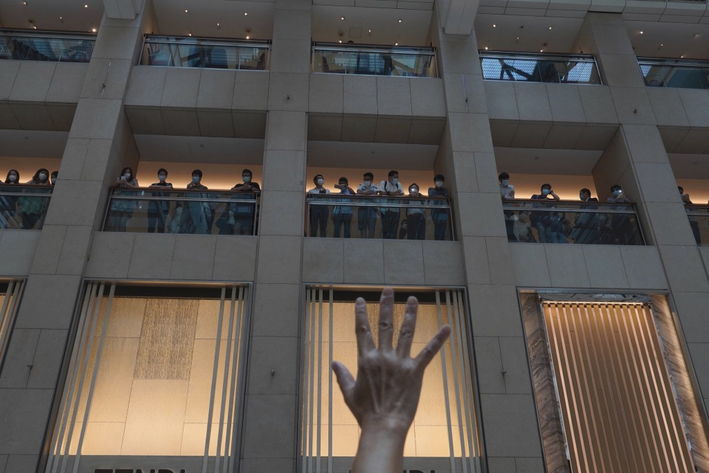 """A protester gestures with five fingers, signifying the """"Five demands - not one less"""" in a shopping mall during a protest against China's national secu..."""