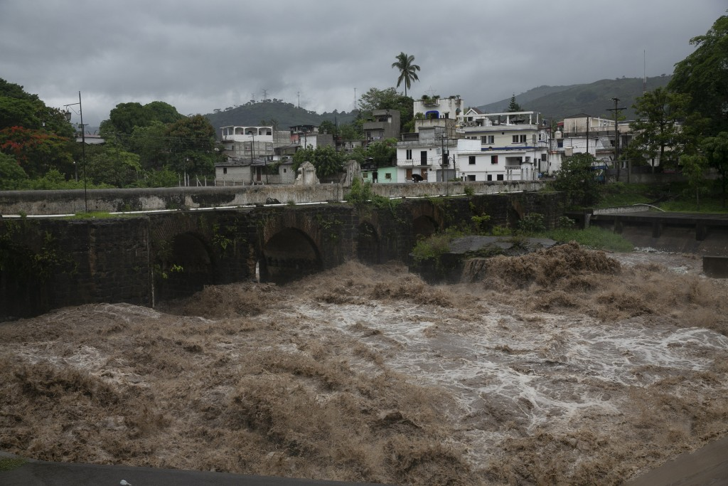 The swollen Los Esclavos River flows violently during tropical storm Amanda in Cuilapa, eastern Guatemala, Sunday, May 31, 2020. The first tropical st...