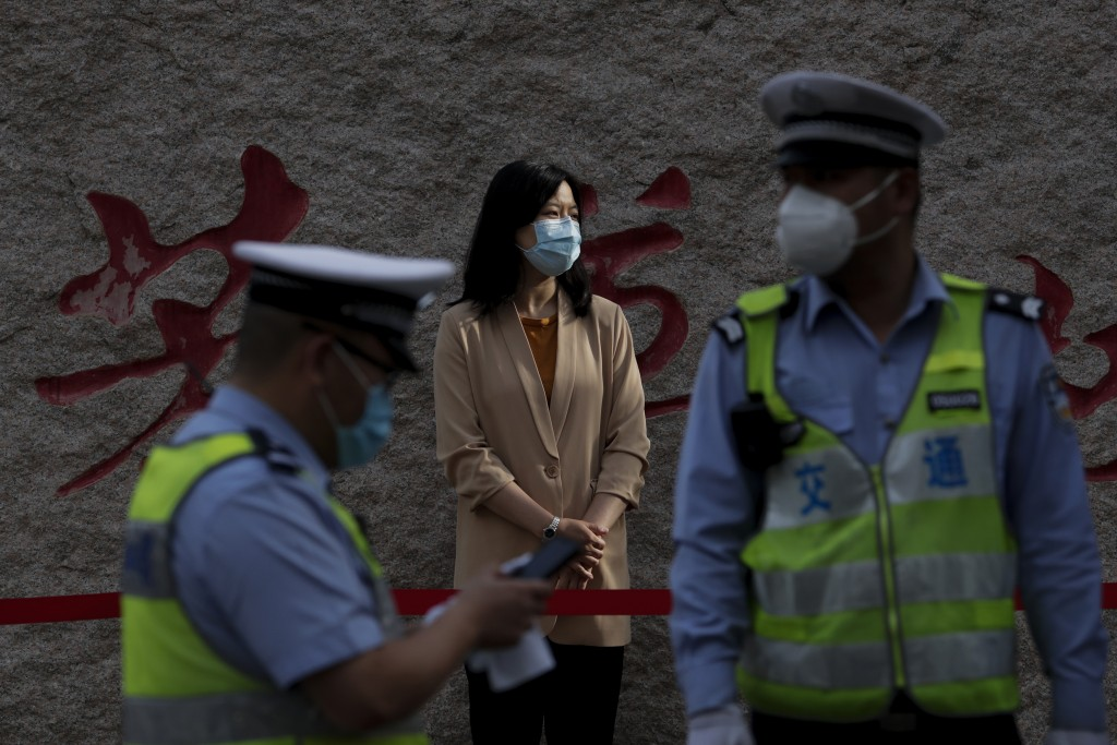 A teacher wearing a protective face mask to help curb the spread of the new coronavirus waits for arrival of the students outside a primary school in ...
