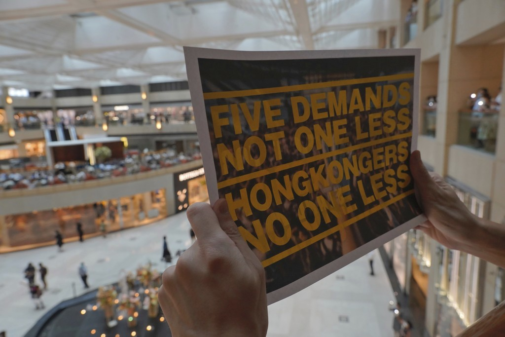 A protester holds a placard in a shopping mall during a protest against China's national security legislation for the city, in Hong Kong, Monday, June...