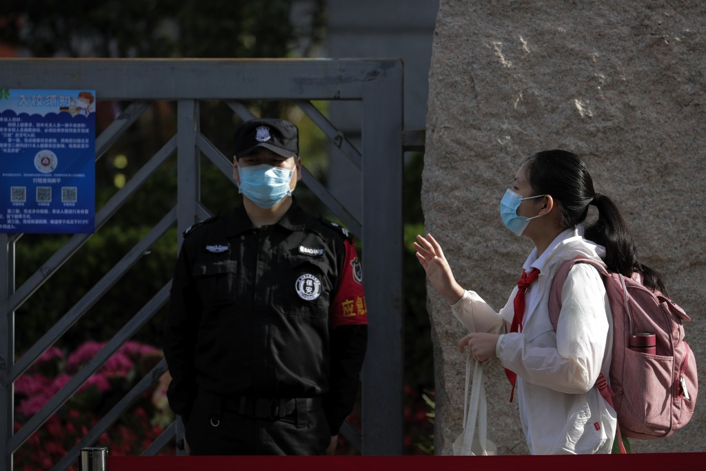 A student wearing a protective face mask to help curb the spread of the new coronavirus waves to teachers as she arrives for the reopening of a primar...