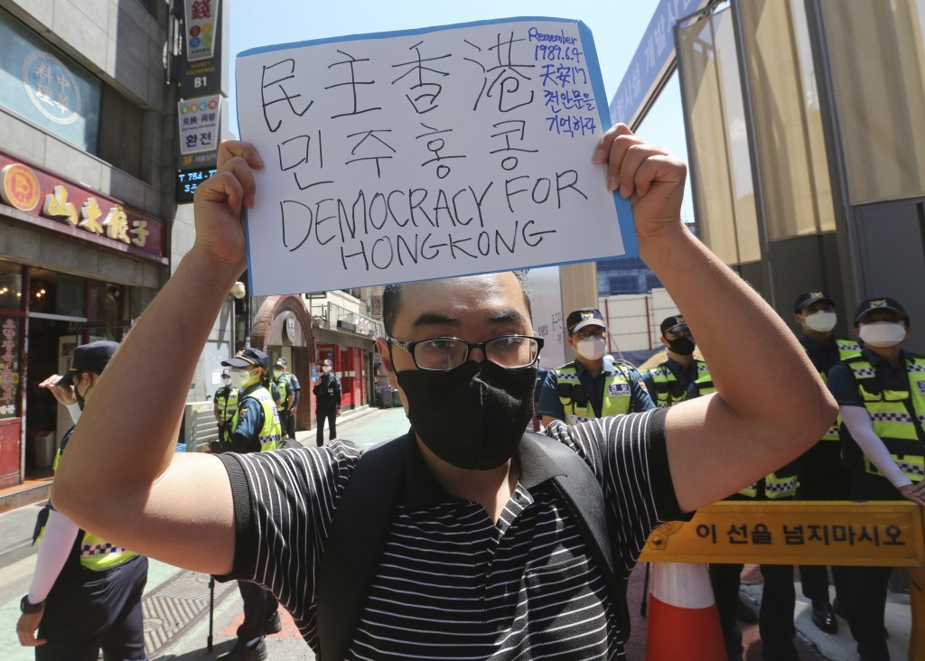 A South Korean protester holds up a notice during a rally to support Hong Kong protests near the Chinese embassy in Seoul, South Korea, Monday, June 1...