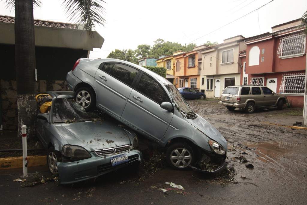 Vehicles stand damaged by an Acelhuate River flash flood at a neighborhood in San Salvador, El Salvador, Sunday, May 31, 2020. According to the Minist...