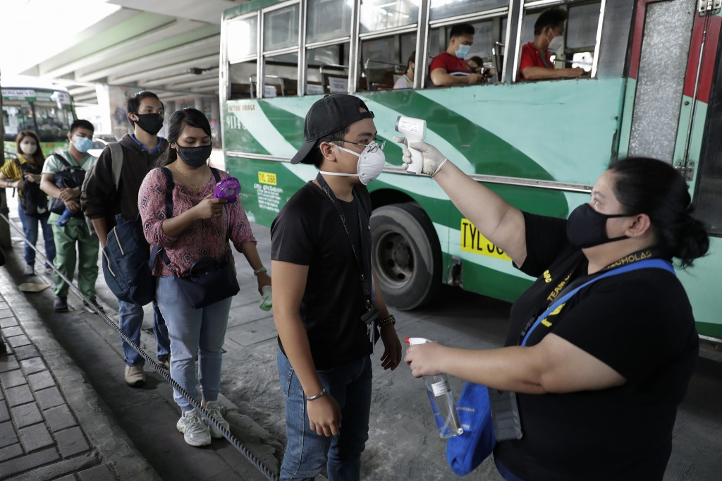 People havetemperatures checked before boarding bus in Manila, Philippines.