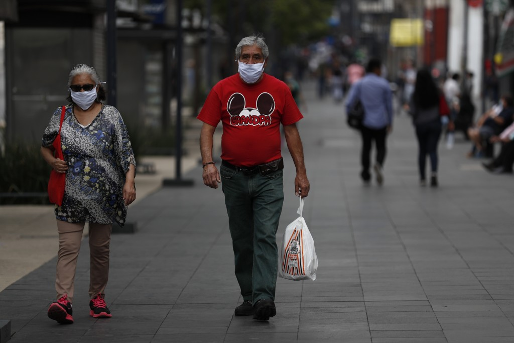 People stroll down Juarez Avenue in central Mexico City, Sunday, May 31, 2020. Mexico's capital plans to reopen certain sectors of the economy and pub...
