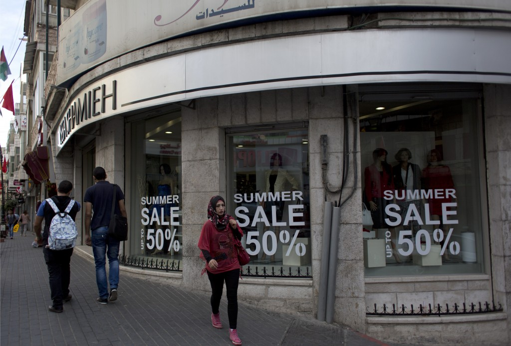FILE - In this Sept. 29, 2015, file photo, Palestinians walk past a boutique in the West Bank city of Ramallah. The World Bank says the Palestinian ec...