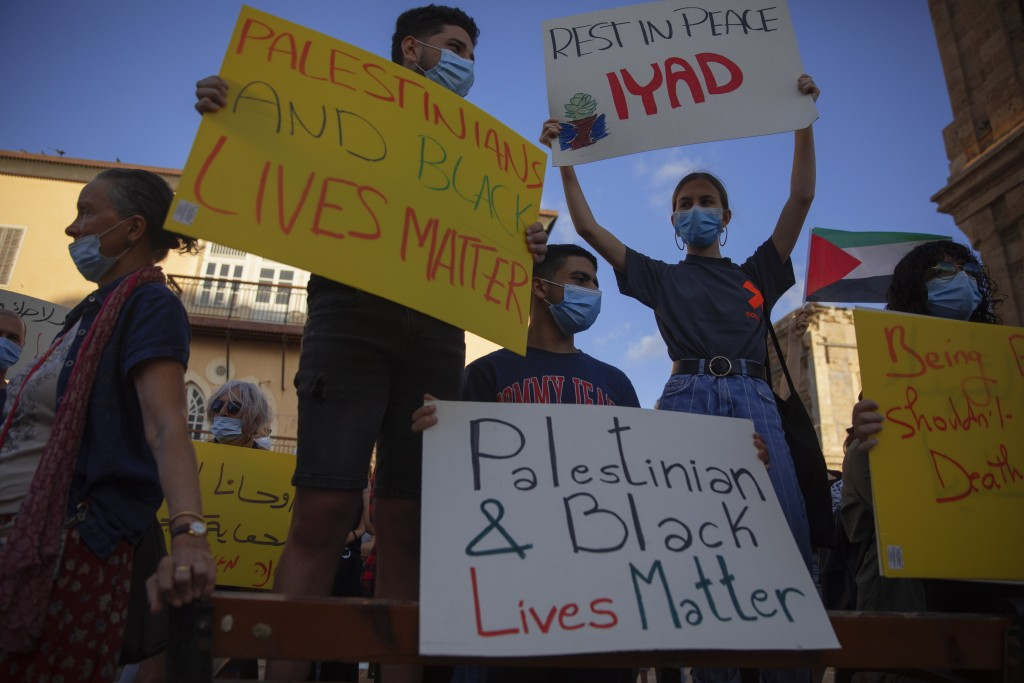 Protesters hold signs during a demonstration against the Israeli police after border police officers shot and killed Iyad al-Halak, an unarmed autisti...