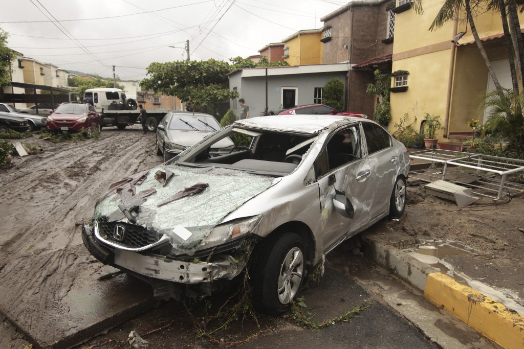 Vehicles stand damaged by the Acelhuate River after a flash flood at a neighborhood in San Salvador, El Salvador, Sunday, May 31, 2020. According to t...