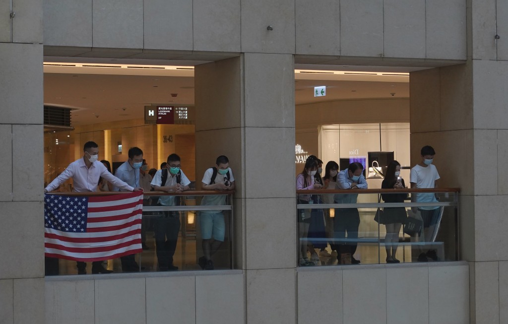 Protesters displays a U.S. flag in a shopping mall during a protest against China's national security legislation for the city, in Hong Kong, Monday, ...