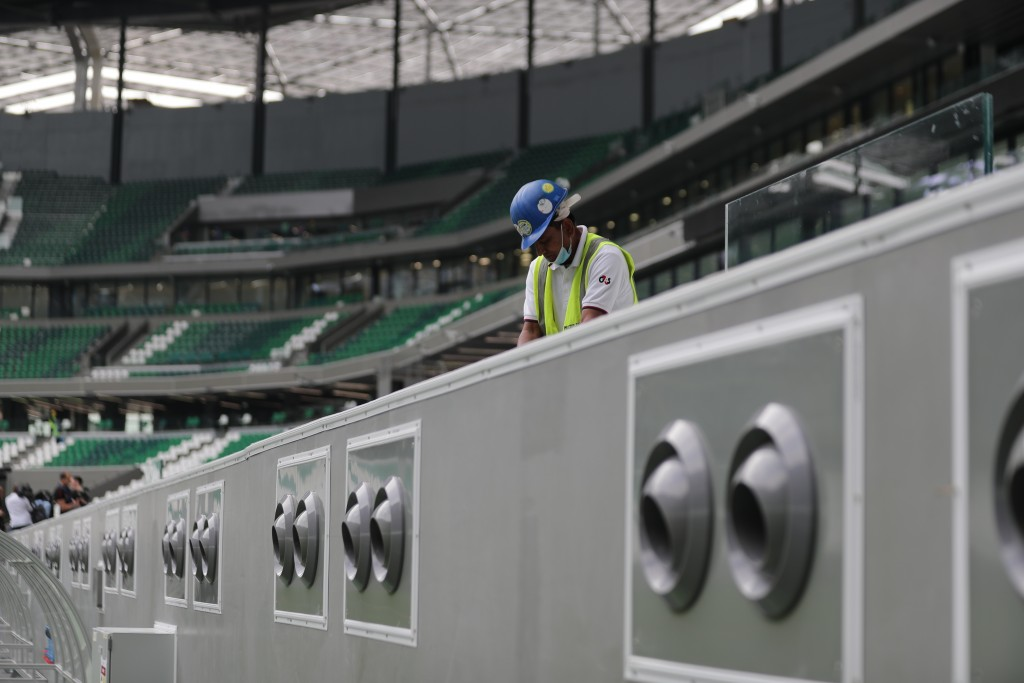 FILE - In this Dec. 15, 2019, file photo, a worker cleans above air conditioning vents at Qatar Education Stadium, an open cooled stadium with a 45,35...