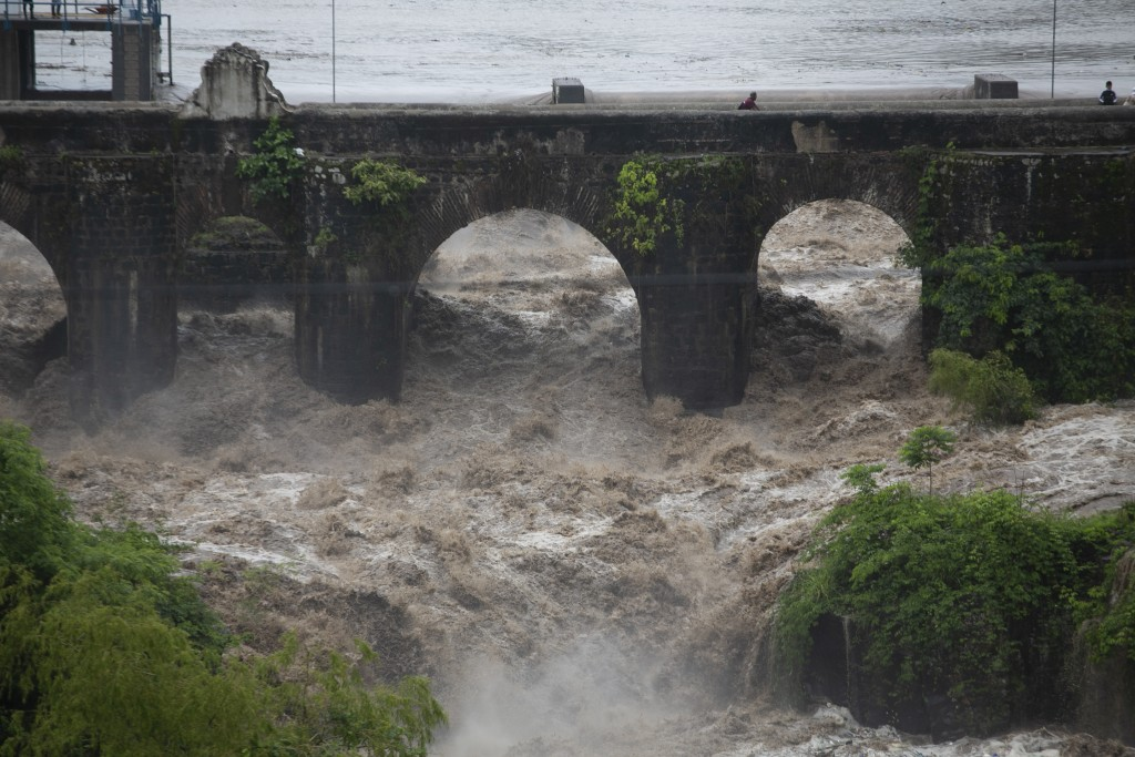The swollen Los Esclavos River flows violently under a bridge during tropical storm Amanda in Cuilapa, eastern Guatemala, Sunday, May 31, 2020. The fi...