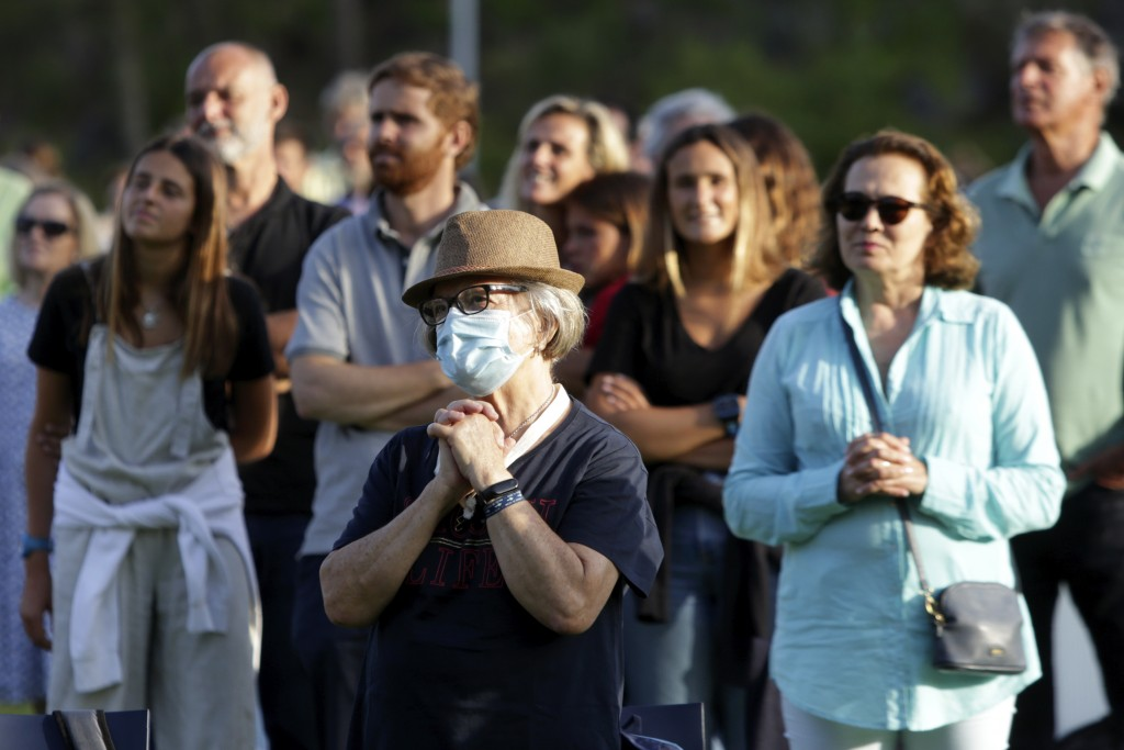 Worshippers attend an outdoor mass at the hippodrome in Cascais, outside Lisbon, Sunday, May 31, 2020. As the government eases the coronavirus lockdow...