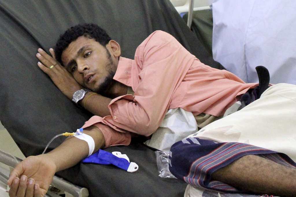 FILE - In this May 12, 2020 file photo, a Yemeni man receives treatment as he lies on a bed at a hospital in Aden, Yemen. Aid organizations are making...