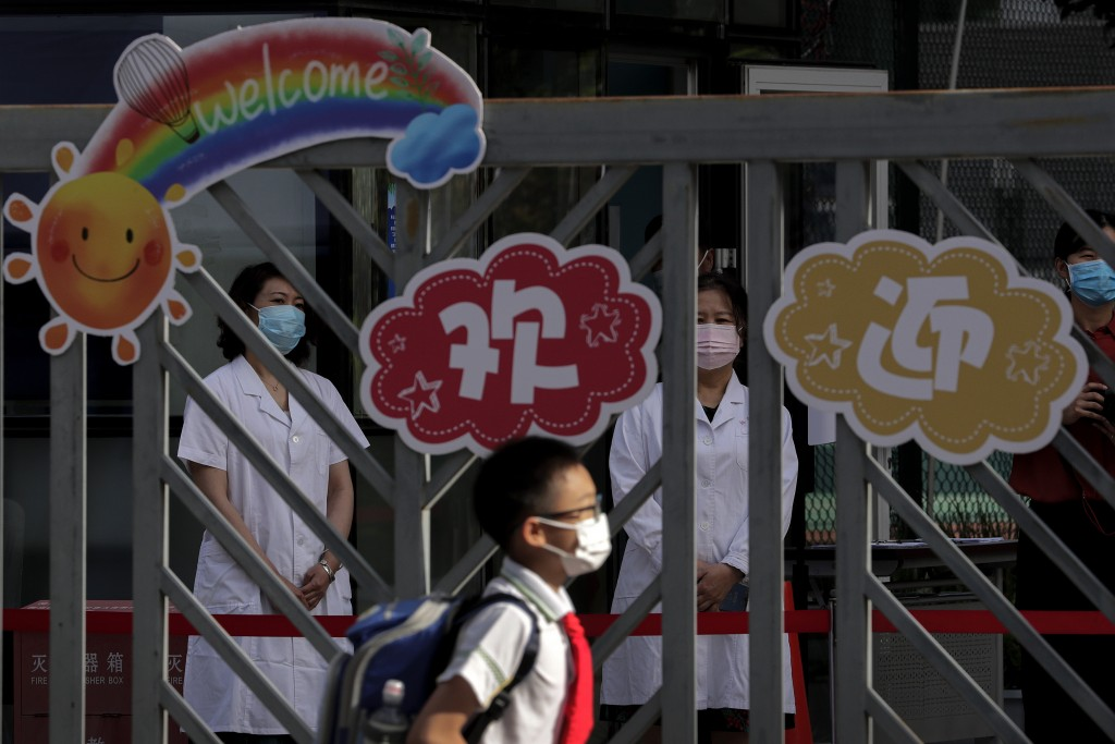 Medical worker wearing protective face masks to help curb the spread of the new coronavirus wait for the arrival of the students at a primary school i...