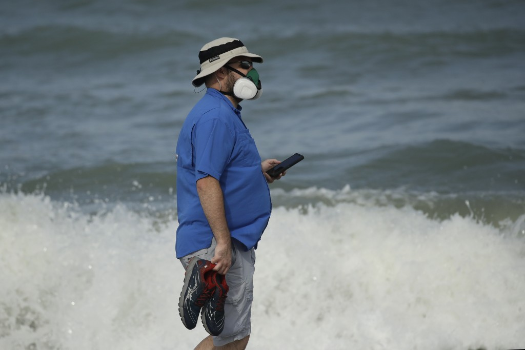 A man wears a mask to help prevent the spread of the coronavirus as he walks alone on the beach Sunday, May 31, 2020, at Satellite Beach, Fla. (AP Pho...
