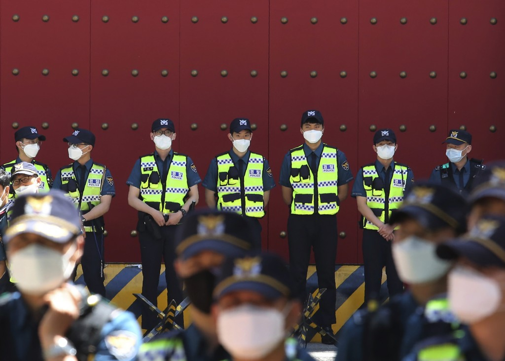 Police officers wearing face masks to help protect against the spread of the new coronavirus stand guard in front of the Chinese embassy in Seoul, Sou...