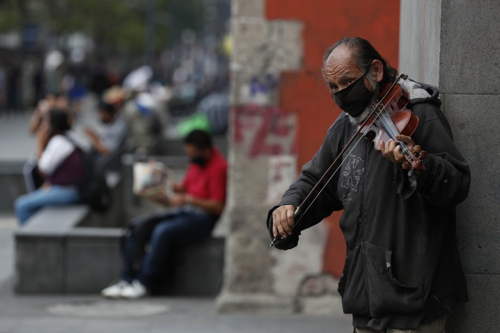 Fernando Castro, 59, plays a violin to earn tips from passerby, on Juarez Avenue in Mexico City, Sunday, May 31, 2020. Castro said he spent nearly two...