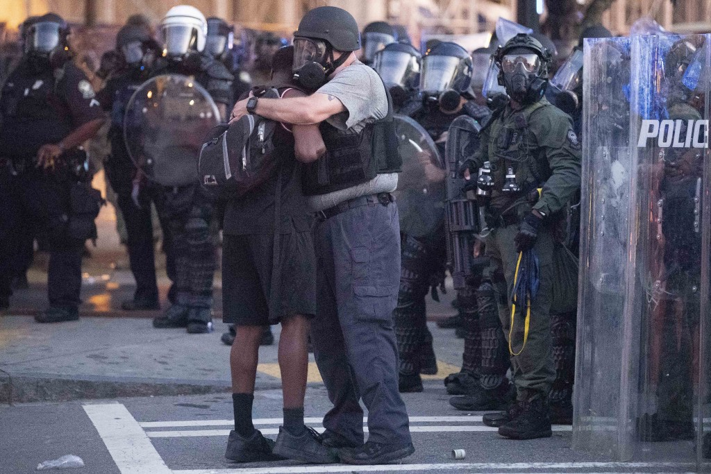A police officer embraces a protester who helped disperse a crowd of people during a demonstration Monday, June 1, 2020, in Atlanta over the death of ...
