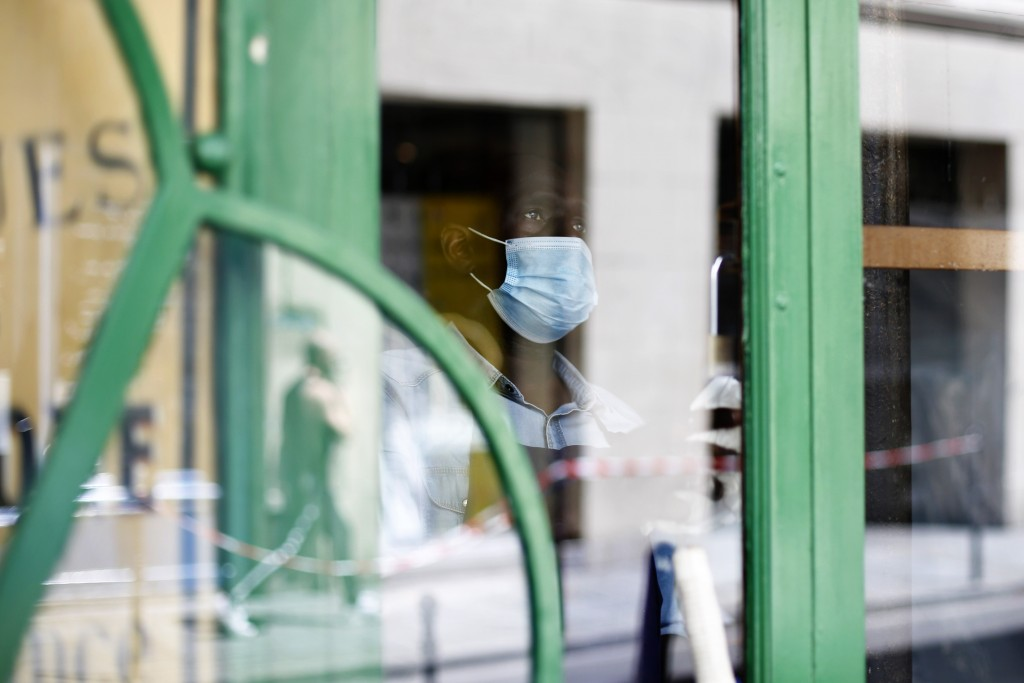 A cafe employee, Djibril, cleans the window of a closed cafe, in Paris, Monday, June 1, 2020. Parisians who have been cooped up for months with take-o...