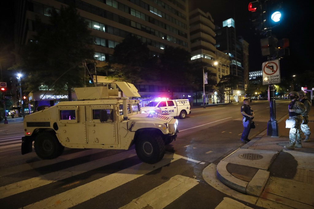 A military Humvee blocks an intersection along K Street in downtown Washington as demonstrators protest the death of George Floyd, Monday, June 1, 202...