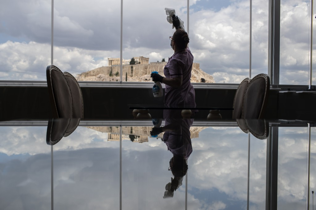 Hotel worker Mailinda Kaci cleans the windows in a restaurant area at the Acropolian Spirit Hotel in central Athens as the ancient Acropolis is seen i...