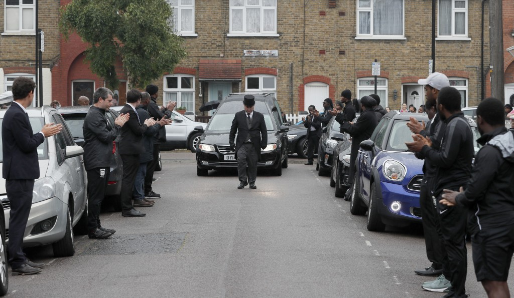 Grass roots soccer referees form a guard of honour and clap for the hearse carrying Jermaine Wright, a referee of the Hackney Marshes grassroots footb...