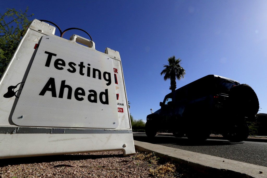 FILE - In this May 23, 2020, file photo, a vehicle arrives at COVID-19 testing site at Steele Indian School Park, in Phoenix. Coronavirus cases are ri...