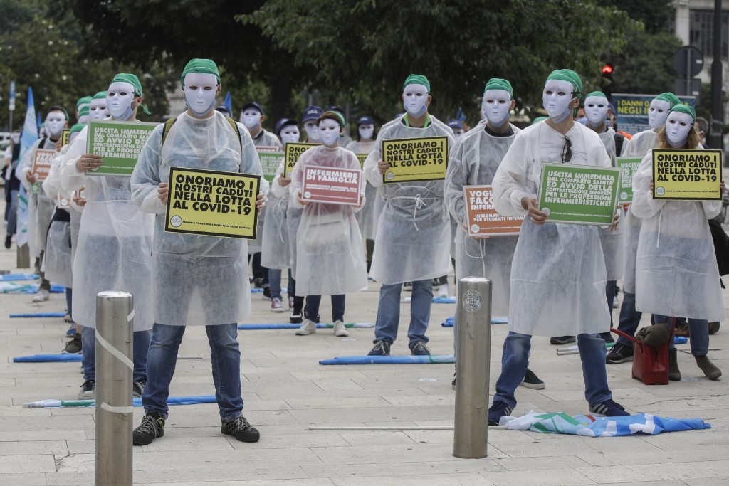 """Nurses belonging to NurSind union hold up signs with writing reading in Italian """"We honor our fallen in the fight against COVID-19"""" as they stage a pr..."""