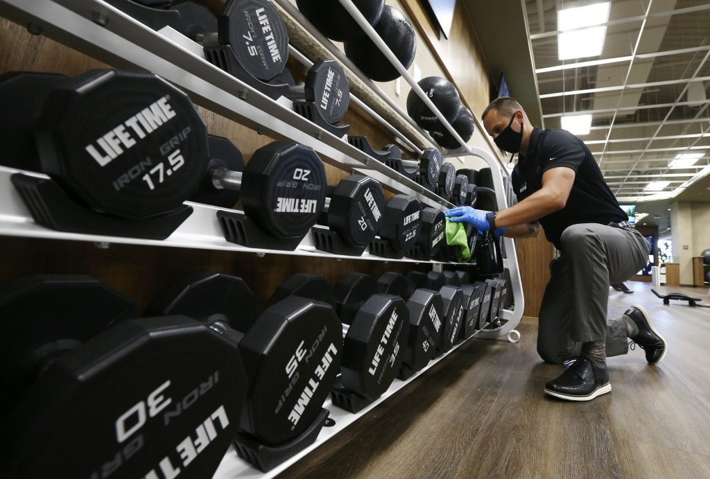 FILE - In this May 18, 2020, file photo, Jason Nichols, facilities operation manager at Life Time, disinfects hand weights at the Life Time Biltmore a...