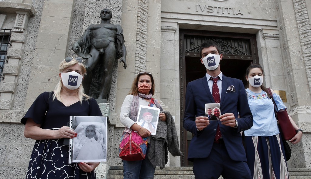 From left, Laura Capella, Nicoletta Bosica, Stefano Fusco and Arianna Dalba holds pictures of their relatives, victims of COVID-19, as they stand in f...