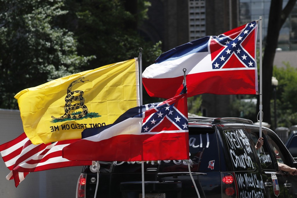 In this April 25, 2020 photo, Mississippi state flags are positioned on a vehicle amid an arrangement with the American flag and a Gadsden flag during...