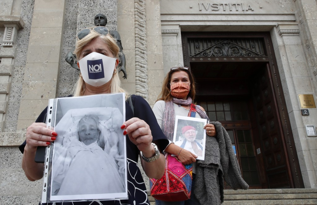 Laura Capella, left, holds up a picture of her father Mario and Nicoletta Bosica holds a photograph of her father Ernani, victims of COVID-19, as they...