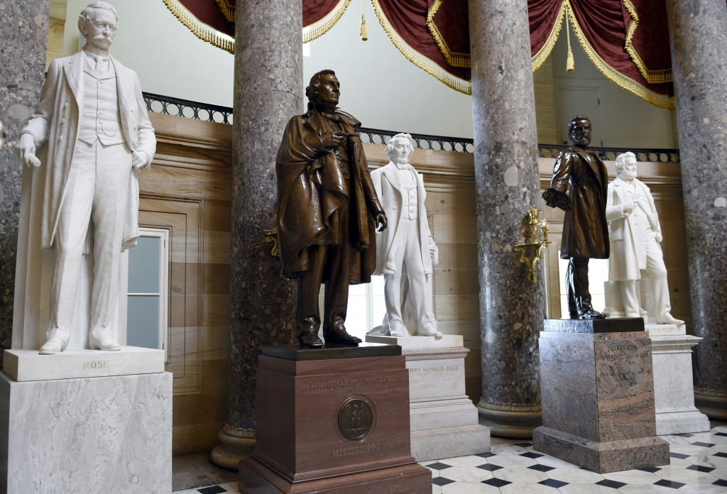 FILE - In this June 24, 2015 file photo, a statue of Jefferson Davis, second from left, president of the Confederate States from 1861 to 1865, is on d...