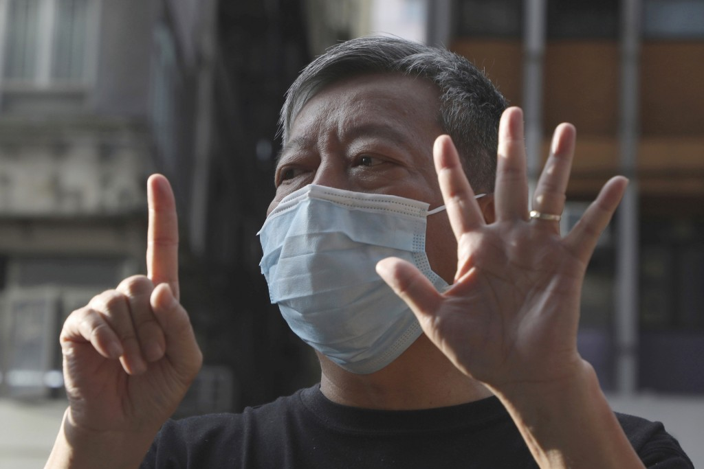 """FILE - In this May 1, 2020, file photo, pro-democracy activist Lee Cheuk-Yan displays opened palm with five fingers, signifying the """"Five demands - no..."""