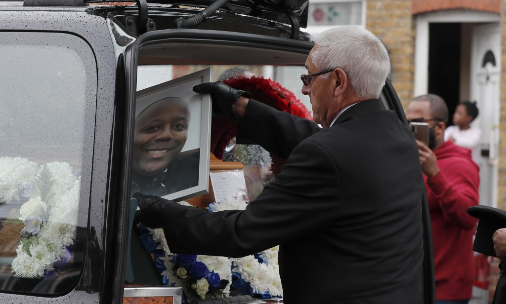 Staff of a funeral service place a picture of Jermaine Wright, a referee of the Hackney Marshes grassroots football league who died of COVID-19, into ...