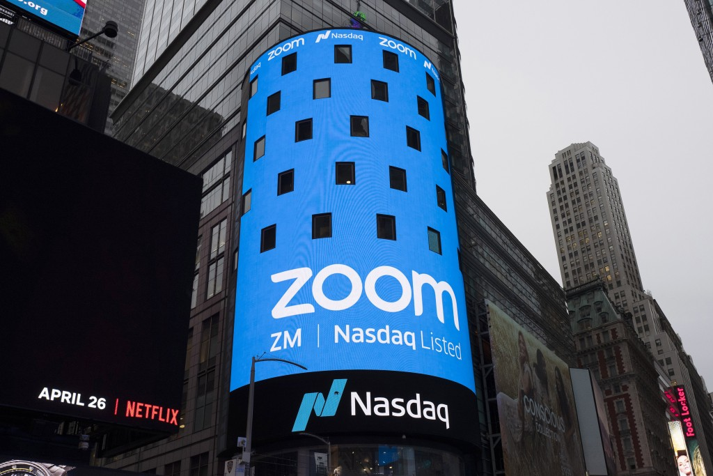 FILE - This April 18, 2019, file photo shows a sign for Zoom Video Communications ahead Nasdaq IPO in New York.  Video app company Zoom said Thursday,...