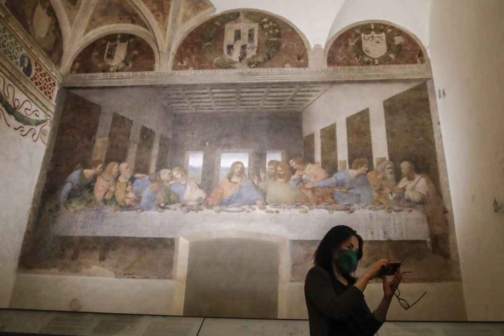 A visitor takes a selfie as she admires Leonardo da Vinci's mural painting ' The Last Supper ', dating back to 1495-1498 and preserved at the ex-Renai...
