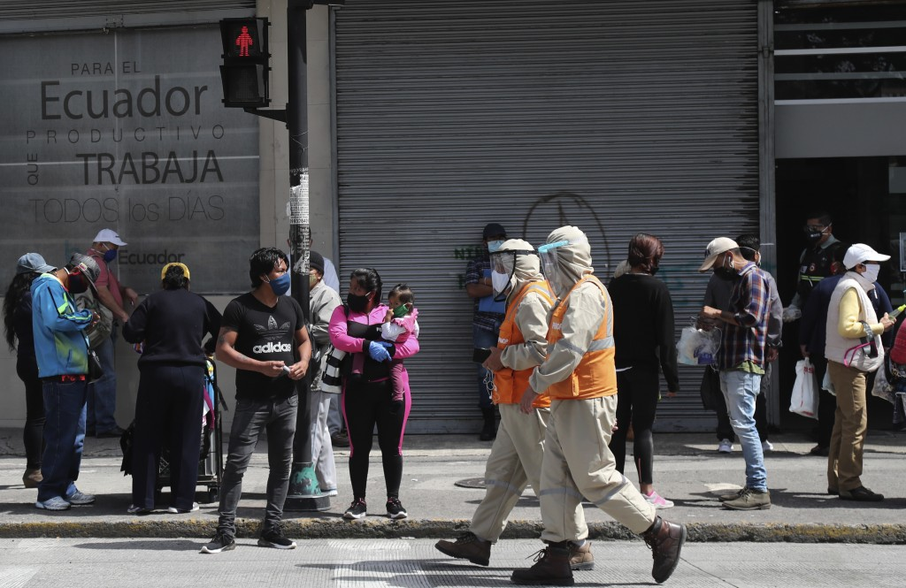 Workers dressed in protective from head to toe walk past pedestrians wearing protective face masks as a mandatory measure to help curb the spread of t...